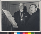 Gerard F. Yates, S.J. (on left), reviews his citation for the Patrick Healy Award with Georgetown University President Robert J. Henle, S.J. (on right)